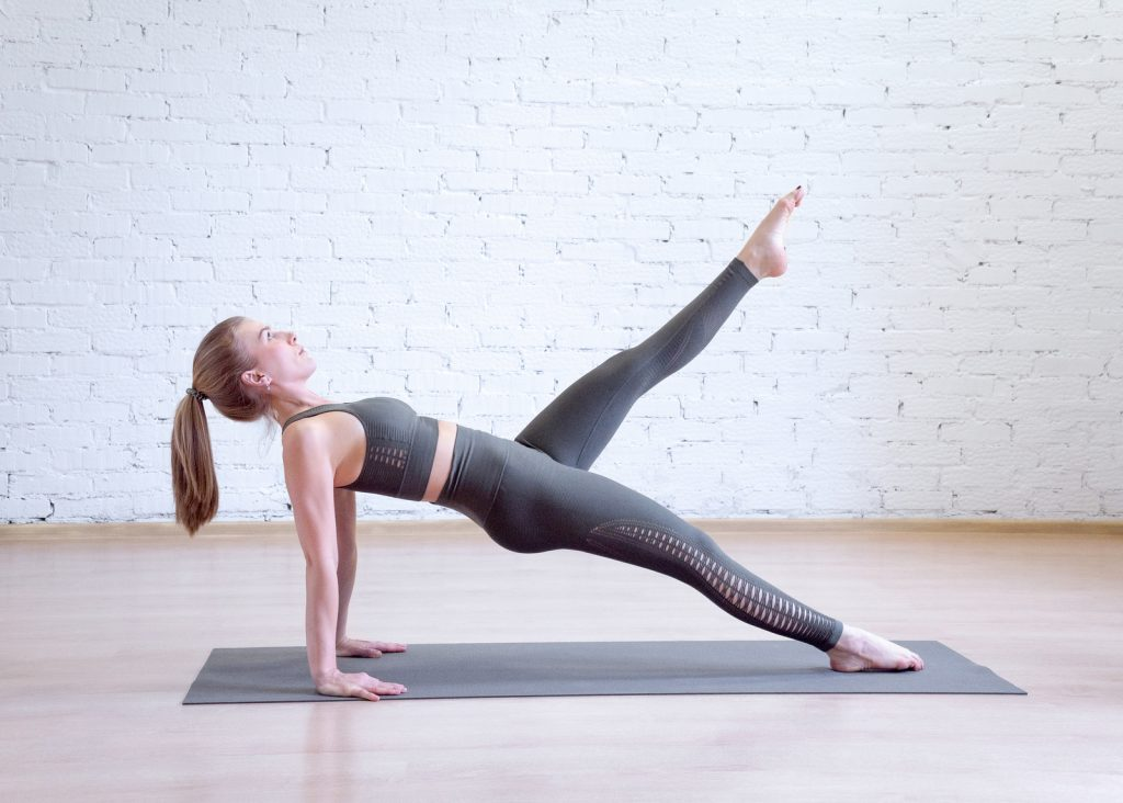 Caucasian woman doing reverse plank on mat in pilates studio, one leg up, side view.